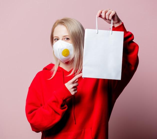 Vrouw in ffp2 anti-stof standaard gezichtsmasker houdt boodschappentas op roze achtergrond