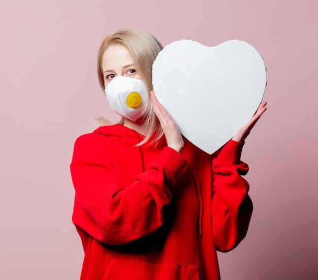 Vrouw in ffp2 anti-stof standaard gezichtsmasker houdt hartvorm banner op roze achtergrond