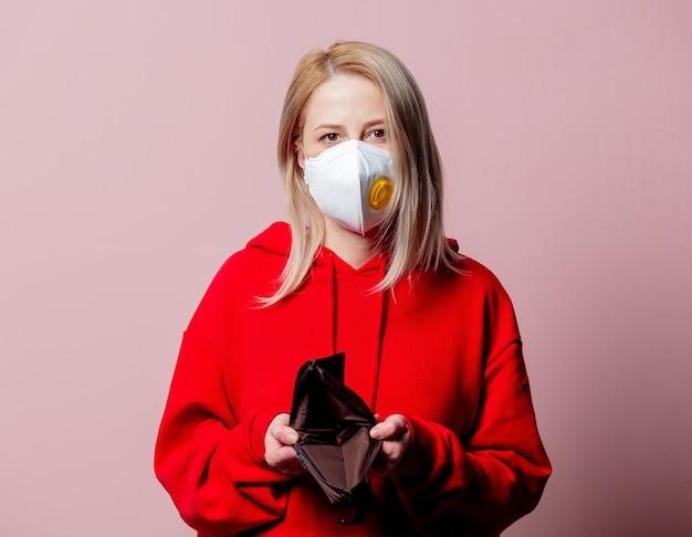 Vrouw in ffp2 anti-stof standaard gezichtsmasker houdt lege portemonnee op roze achtergrond