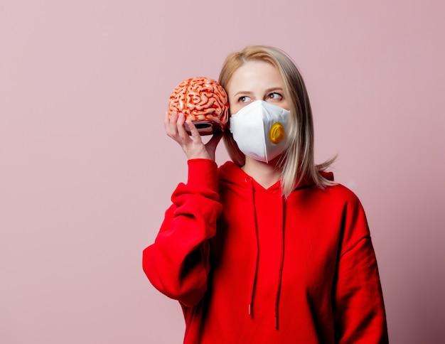 Vrouw in ffp2 anti-stof standaard gezichtsmasker houdt menselijk brein vast