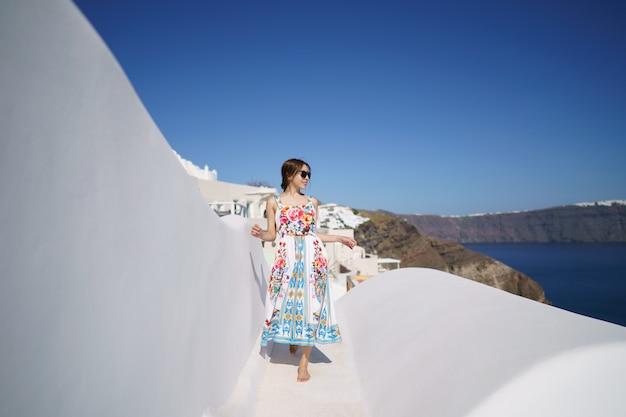 Vrouw in flora jurk op wit dak van een gebouw in santorini, griekenland.