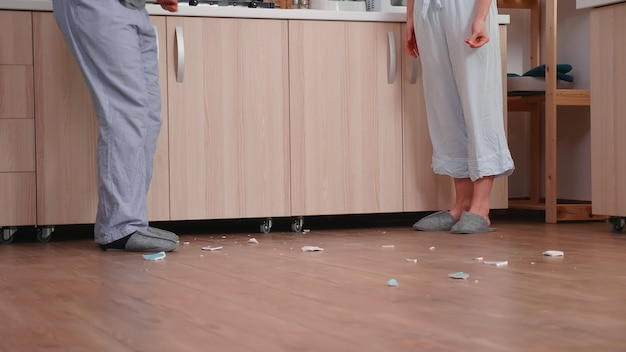 Vrouw in frustratie die plaat breekt terwijl ze ruzie maakt met haar man. . man en vrouw schreeuwen gefrustreerd tijdens thuisgesprek.