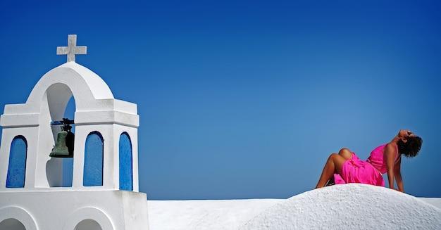 Vrouw in fuchsiakleding op blauwe hemelachtergrond van santorini, oia