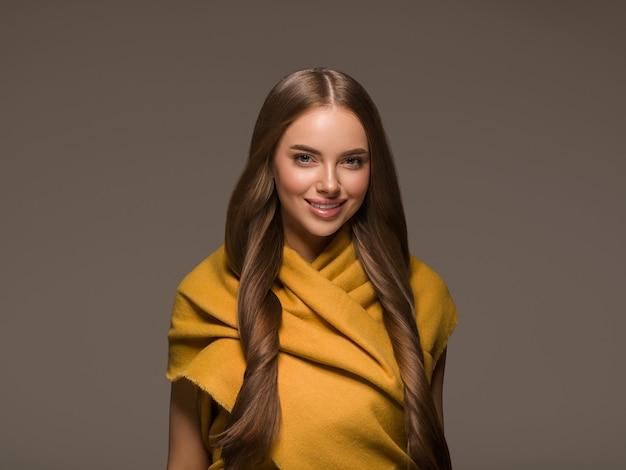 Vrouw in gebreide kleding geel herfst winter stijl lang haar. kleur achtergrond bruin
