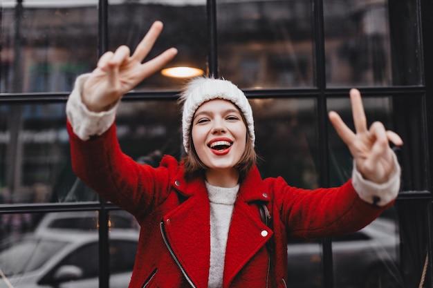 Vrouw in gebreide muts en rode warme jas lacht, vredestekens tonen en op zoek naar camera tegen de achtergrond van het raam met zwart houten frame.