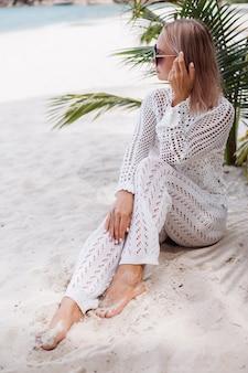 Vrouw in gebreide witte kleren op strand