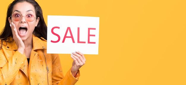 Vrouw in geel jasje kopie ruimte verkoop concept