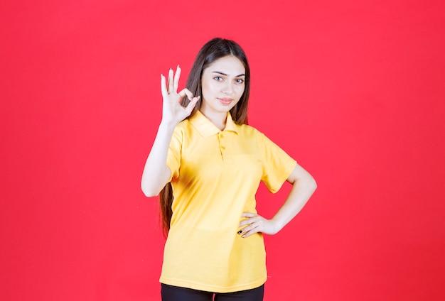 Vrouw in geel overhemd dat zich op rode muur bevindt en positief handteken toont.