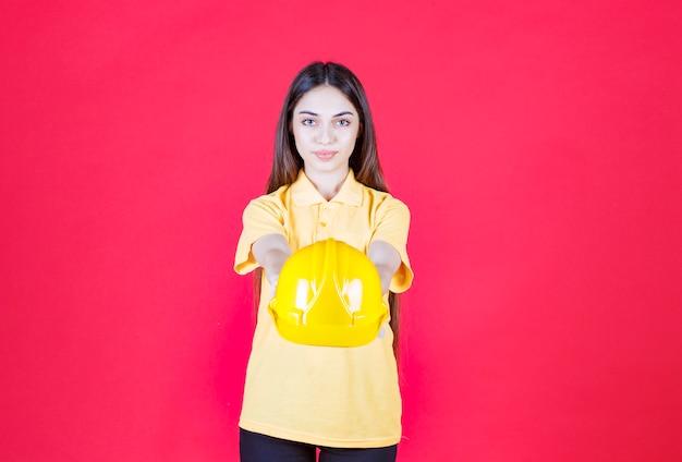Vrouw in geel shirt met een gele helm en belt haar collega om het te presenteren.