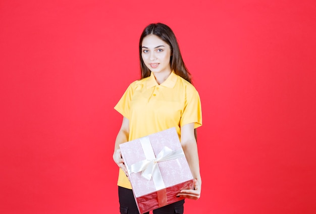 Vrouw in geel shirt met een roze geschenkdoos.