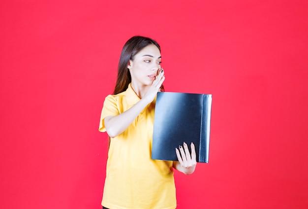 Vrouw in geel shirt met een zwarte map, wijzend en haar collega bellend.