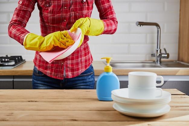 Vrouw in gele beschermende handschoen met borden, borden en doek, houten tafel, keuken achtergrond. wassen en schoonmaken concept.