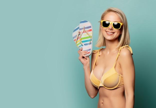 Vrouw in gele bikini en zonnebril met wipschakelaars