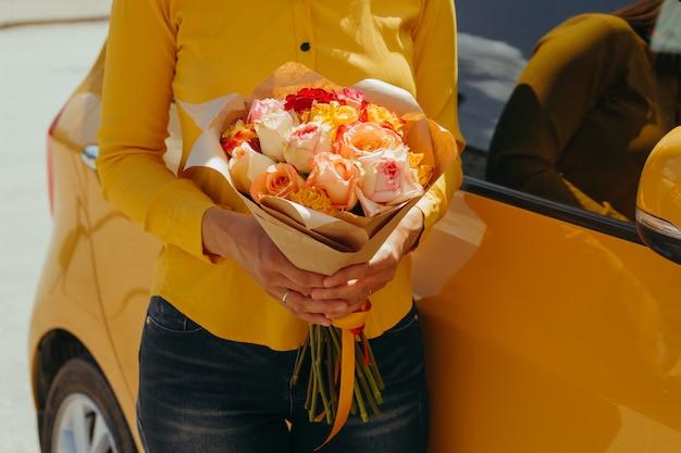 Vrouw in gele blouse met boeket van gele rozen dichtbij gele auto