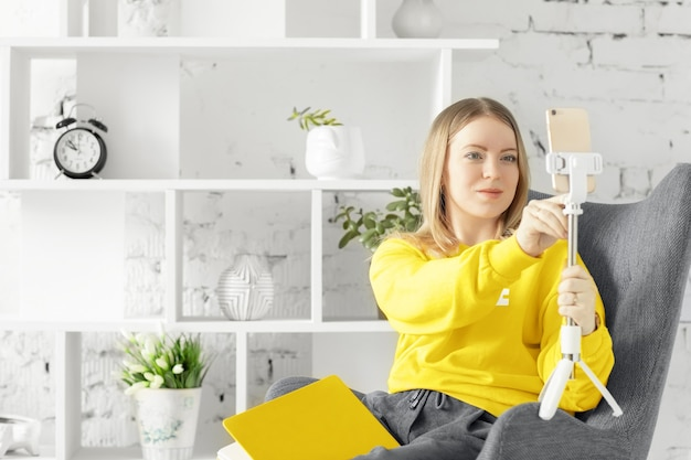 Vrouw in gele blouse zit ontspannen op grijze bank met behulp van smartphone. pantone-kleur van het jaar 2021