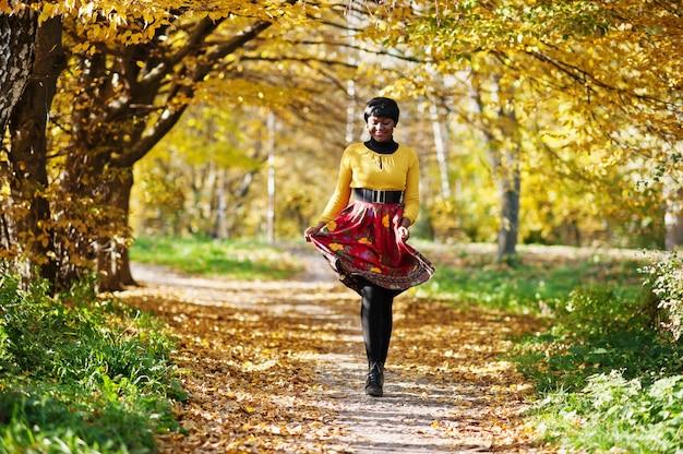 Vrouw in gele en rode kleding bij het gouden park van de de herfstdaling