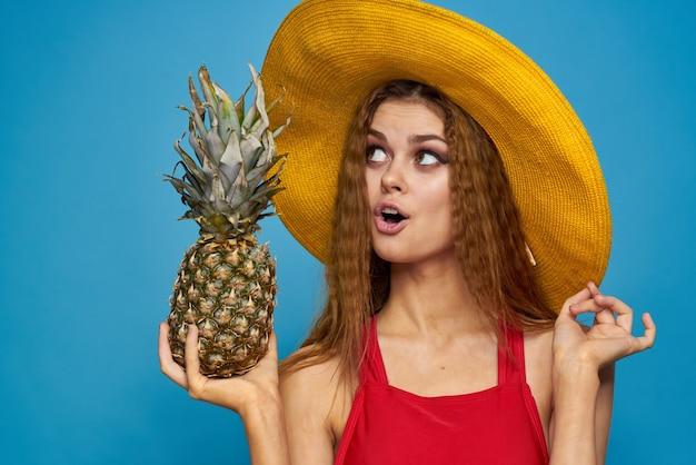 Vrouw in gele hoed met ananas in handen emoties leuke levensstijl zomer fruit blauw