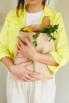 Vrouw in gele jas, permanent met winkelen papieren zak vol verse groenten en fruit thuis