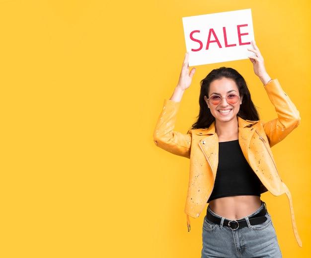 Vrouw in gele jas verkoop banner kopie ruimte