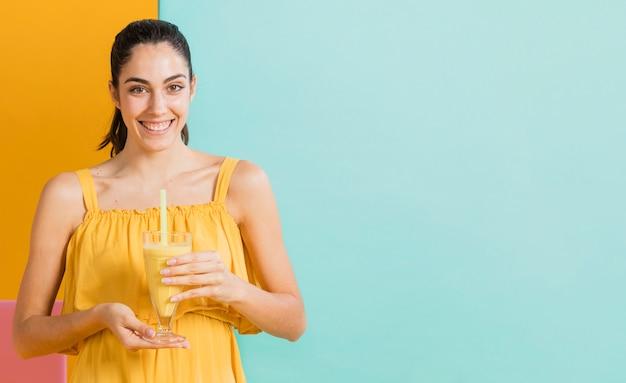 Vrouw in gele jurk met een glas sap