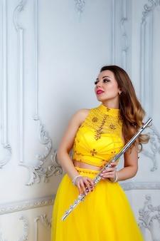 Vrouw in gele jurk met fluit op licht gestructureerde achtergrond