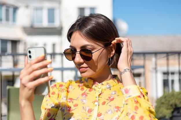 Vrouw in gele jurk op terras in zomerterras met mobiele telefoon op zonnige dag