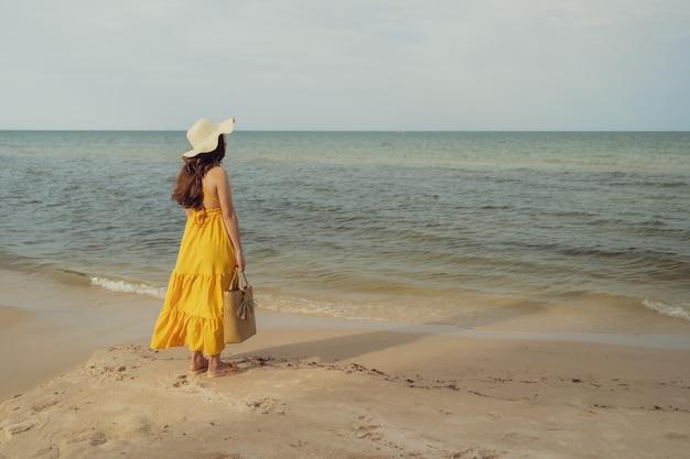 Vrouw in gele jurk staande op het strand met wind waait