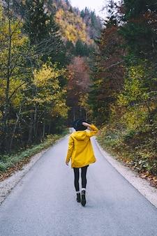 Vrouw in gele regenjas die op weg in de herfstbos loopt jong wandelaarmeisje in aard in openlucht