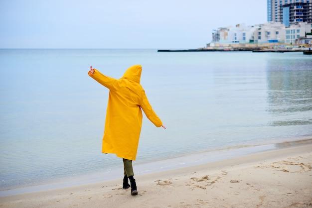 Vrouw in gele regenjas staat alleen met handen in een vliegtuig pose