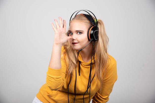 Vrouw in gele sweater die haar hand op grijze achtergrond toont.