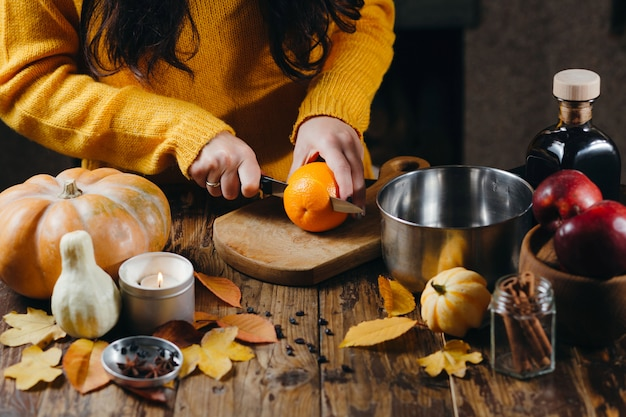 Vrouw in gele trui oranje snijden voor glühwein.