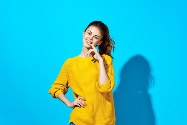 Vrouw in gele trui poseren mode kapsel blauwe achtergrond