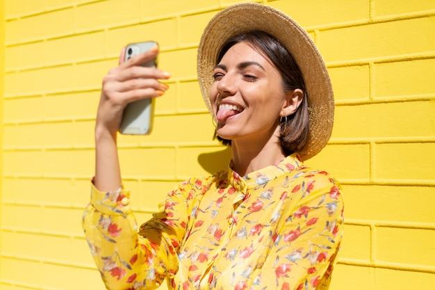 Vrouw in gele zomerjurk en hoed op gele bakstenen muur kalm en positief bedrijf mobiele telefoon toont tong