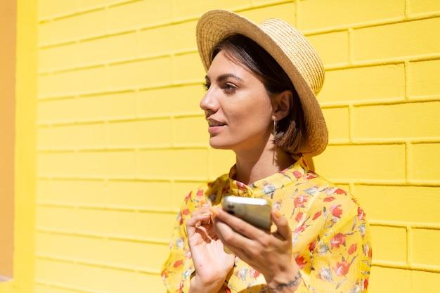 Vrouw in gele zomerjurk en hoed op gele bakstenen muur kalm en positief bedrijf mobiele telefoon