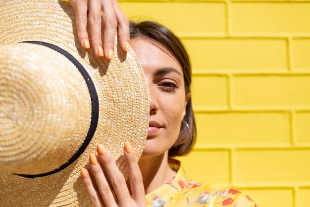 Vrouw in gele zomerjurk en hoed op gele bakstenen muur kalm en positief, geniet van zonnige zomerdagen