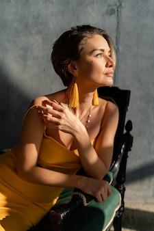 Vrouw in gele zomerjurk met kort kapsel in binnenkamer betonnen muur poseren