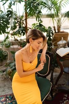 Vrouw in gele zomerjurk met kort kapsel in boho vintage stijl interieur kamer poseren