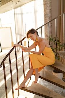 Vrouw in gele zomerjurk met kort kapsel zittend op trap poseren