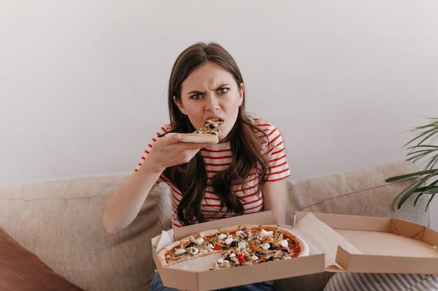 Vrouw in gestreept overhemd met hongerige blik bijt verse pizza