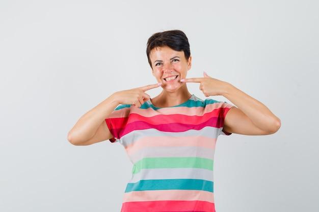 Vrouw in gestreept t-shirt wijzend op haar tanden en ziet er vrolijk uit