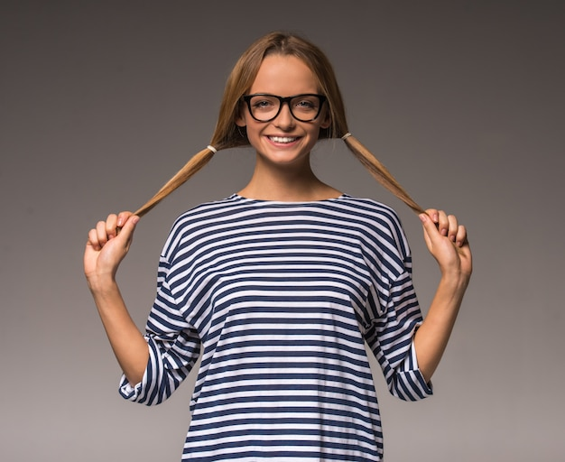 Vrouw in gestreepte kleding en bril houdt twee staarten.