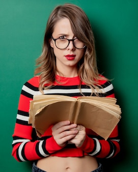 Vrouw in gestreepte sweater en glazen met boek