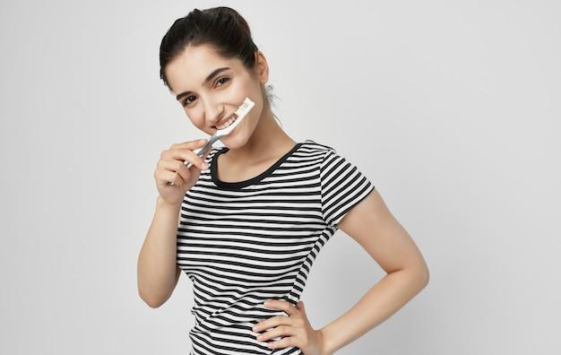 Vrouw in gestreepte t-shirt tandenborstel mondhygiëne gezondheid.