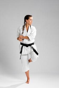 Vrouw in gevechtspositie die het witte uniform op grijze achtergrond draagt