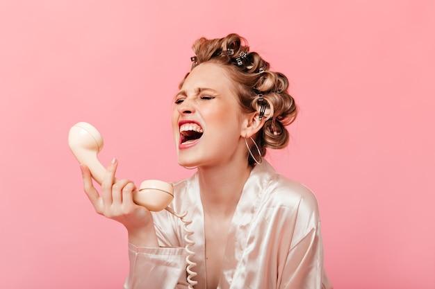 Vrouw in gewaad schreeuwt en huilt, met telefoonhoorn op roze muur