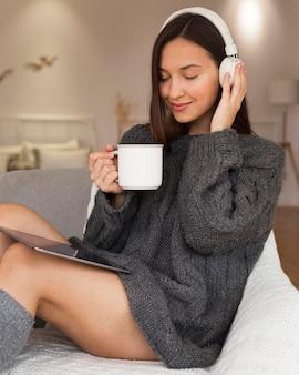 Vrouw in gezellige kleding, zittend in een stoel met mok en koptelefoon