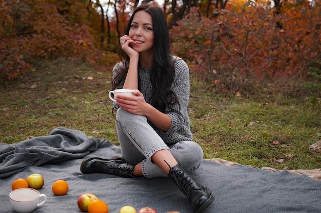 Vrouw in gezellige trui met een kopje met warme drank. theetijd buitenshuis. herfst sfeer