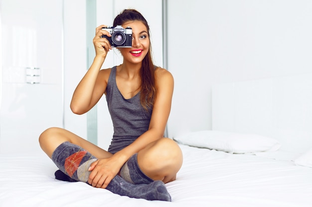 Vrouw in gezellige vrijetijdskleding, zittend op een groot wit bed, en foto's maken op vintage camera