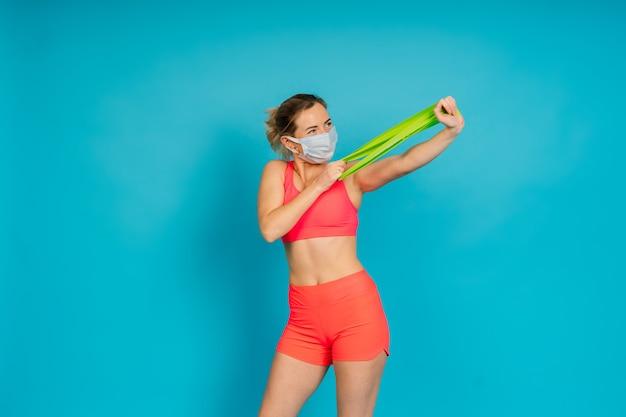 Vrouw in gezichtsbeschermingsmasker en fitnessslijtage geïsoleerd over blauwe achtergrond.