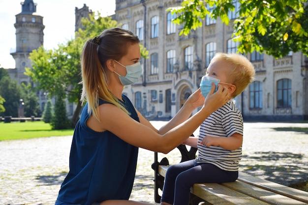 Vrouw in gezichtsmasker draagt beschermend masker aan een jongen die op de bank zit. moeder en zoon. nieuw normaal. terug naar school of kleuterschool.